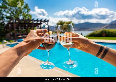 Weine Weinprobe auf einem Weingut Restaurant Terrasse mit Swimmingpool auf den Okanagan Lake wunderschöne Landschaft, während der heißen sonnigen Frühlingstag mit blauem Himmel