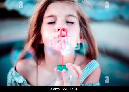 Porträt einer wunderschönen kleinen Mädchen bläst Seifenblasen. Ein Kind spielt mit Blasen, auf grünem Hintergrund. Im Freien