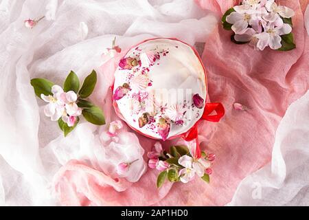 Frohe Ostern Dekoration für Grußkarten. Ostern Kuchen mit weißer Zuckerglasur, Marshmallows, trockene Rose und Frische blooming apple Blumen und rose Farbe Handwerk - Stockfoto