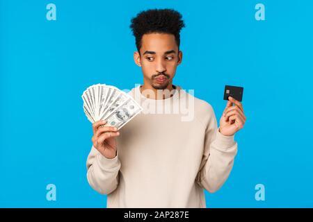 Unentschlossenen und gestörten jungen african-american Kerl mit Blick auf harte Entscheidung, schmollen, ausatmen harte Wahl Macht, Geld und Kreditkarte, betrachten - Stockfoto