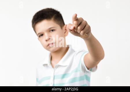 Süße kleine Junge im gestreiften T-Shirt, die Kamera auf weißem Hintergrund. Kind zu Ihnen zeigt. Fokus auf Hand - Stockfoto