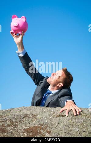 Lächelnd Geschäftsmann halten auf einen treuen rosa Sparschwein Rock wie er oben auf einem felsigen Klippe erreicht. - Stockfoto
