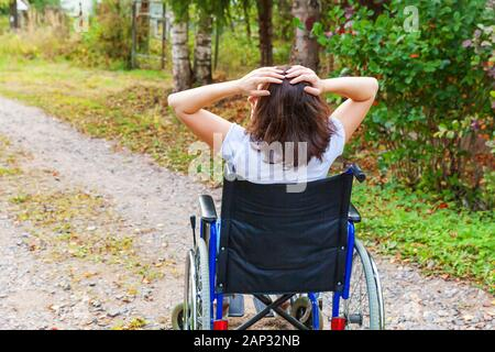Junge glücklich handicap Frau im Rollstuhl auf der Straße im Krankenhaus park Freiheit genießen. Gelähmte Mädchen in ungültig Lehrstuhl für behinderte Menschen draußen in der Natur. Rehabilitation Konzept - Stockfoto
