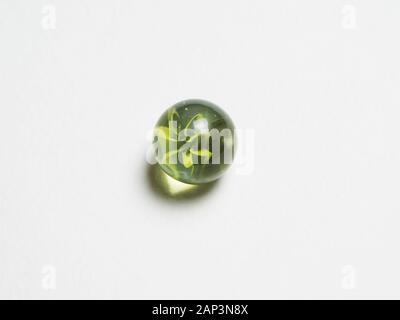 Eine grüne Glaskugel mit ätzenden auf weißem Hintergrund - Stockfoto