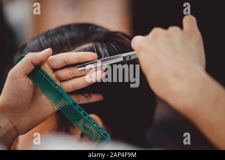 Barbershop-Konzept. Mann barber in den Männern Friseursalon macht Haare mit einer Schere - Stockfoto