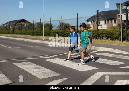 Zwei Schuljungen, die auf einem Fußgängerübergang die Straße überqueren