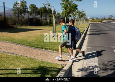 Zwei Schuljungen, die nach dem Überqueren der Straße den Straßenbelag erreichen