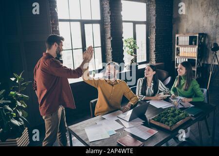 Portrait von vier schönen attraktiven froh aufgeregt fröhlichen fröhlichen professionellen Leuten, Leiter der Handflächen einklatschen Recruitment im Industrial Loft - Stockfoto