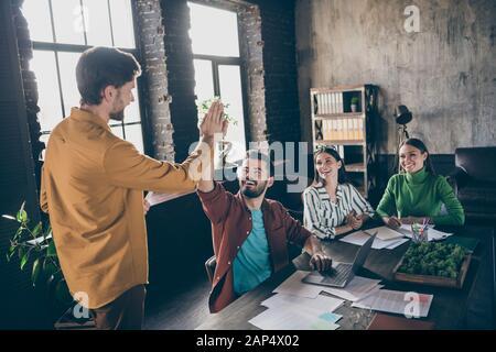 Porträt von vier netten attraktiven fröhlichen fröhlichen Profis IT-Rekrutierer Treffen mit einladenden Handflächen im industriellen Loft-Interieur - Stockfoto