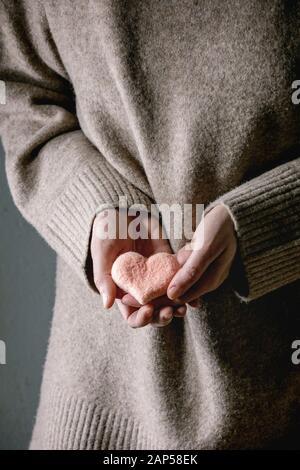 Vielzahl von Nadel gefilzte rosa Herz in weibliche Hände. St Valentines Tag liebe Pflege Grußkarte - Stockfoto