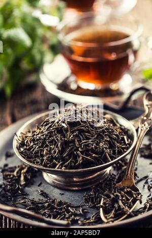 Getrocknete Teeblätter in Schüssel auf rustikalen Holztisch - Stockfoto