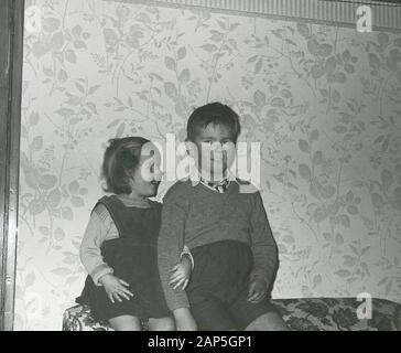 1950er Jahre, historisch, ein Schuljunge und seine Schwester, die auf einem Sofa sitzen, wobei das kleine Mädchen ihren erschreckenden Bruderarm hält, der in seiner Schuluniform, England, Großbritannien, steht. - Stockfoto