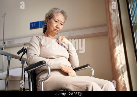 Traurige und depressive asiatische ältere Frau, die allein im Rollstuhl sitzt und im Pflegeheim mit dem Kopf nach unten steht