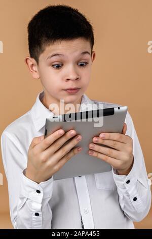 Kleiner überraschter Junge mit Tablet auf hellgelbem Studiohintergrund. - Stockfoto
