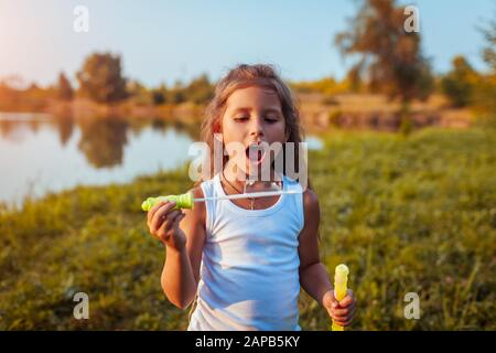 Kleines süßes Mädchen, das Seifenblasen im Sommerpark am Fluss bläst. Nahaufnahme. Kind hat Spaß