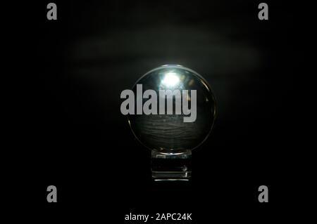 Die Kristallkugel eines Wahrsagers auf schwarzem Hintergrund scheint innen eine Stoffoberfläche zu haben, hinten beleuchtet und an den Rändern glühend. - Stockfoto