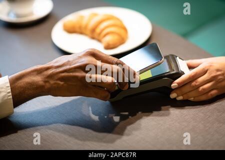 Afro-Geschäftsmann zahlt mit Handy an der Bar - Stockfoto