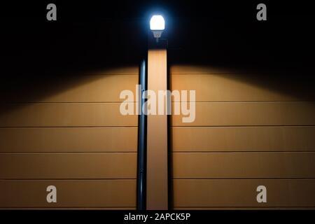Straßenbeleuchtung an der Fassade eines braunen Hauses - Stockfoto