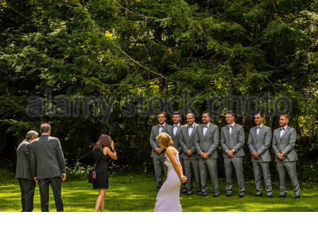 Ein Hochzeitsfotograf nimmt einen Gruppenschuss des Bräutigams und seiner Bräutigam, als seine Mutter und sein Vater (und sein Stiefvater) sich ansehen, bevor er nach dem geht - Stockfoto