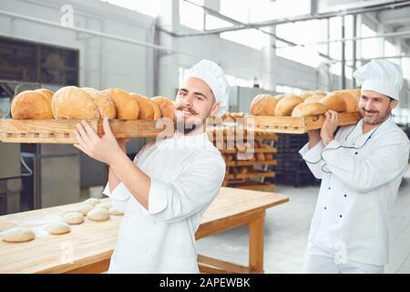 Zwei Bäcker Männer tragen die Fächer mit Brot in der Bäckerei. - Stockfoto