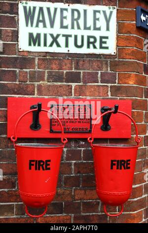 Feuereimer und die Tabakwerbung der Waverley Mixed auf der Wand des Stationsgebäudes, dem Bahnhof Tenterden Town, der Kent & East Sussex Railway, Kent, eng - Stockfoto