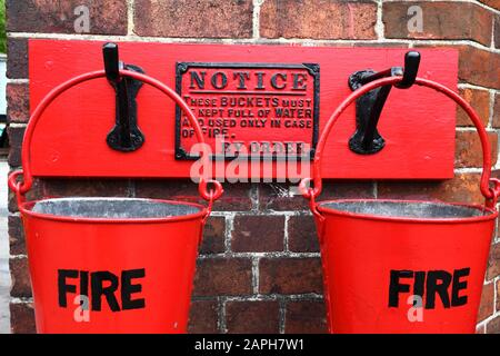 Nahaufnahme der Feuereimer an der Wand des Stationsgebäudes, Bahnhof Tenterden Town, Kent & East Sussex Railway, Kent, England - Stockfoto