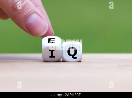 """Hand dreht einen Würfel und ändert den Ausdruck """"IQ"""" (Intelligenzquotient) in """"EQ"""" (Emotionale Intelligenz/Quotient). - Stockfoto"""