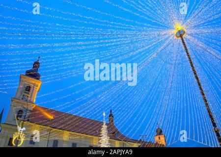 Weihnachtsmarkt und Dekorationsleuchten auf dem Hauptplatz von Sibiu, Siebenbürgen, Rumänien - Stockfoto