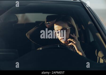 Junge blonde Geschäftsfrau mit Smartphone im Auto - Stockfoto
