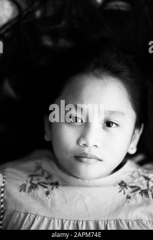 Portrait asiatischer junger Mädchen mit langen Haaren, die mit ernsthaftem Gesicht an der Kamera aussehen. - Stockfoto