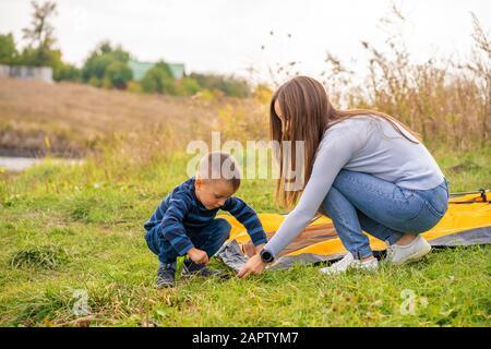Glückliche Familie mit kleinen Sohn Einrichten camping Zelt. Glückliche Kindheit, Camping Trip mit Eltern. Ein Kind hilft dabei, ein Zelt zu setzen. - Stockfoto