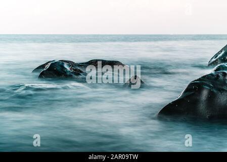 Lange Exposition des Ozeans, die auf Felsen in Tulamen trifft - Stockfoto