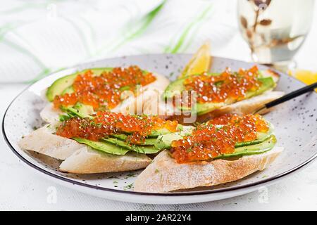 Sandwiches mit lachsrotem Kaviar mit in Scheiben geschnittenem Avocado. Sandwich zum Mittagessen. Hochwertige Lebensmittel. - Stockfoto
