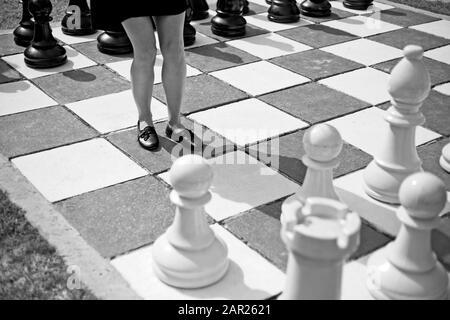 Ein grauer Schuß eines Weibchens, das inmitten eines großen Schachbretts steht - Stockfoto