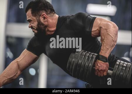 Starker junger bärtiger kaukasischer Mann in schwarzer Sportbekleidung, der schwere Hanteln mit einer Hand trainiert, und Arme im Sporttraining zieht