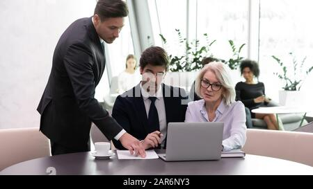Selbstbewusster männlicher Vorgesetzter hilft Teamkollegen verschiedener Altersgruppen. - Stockfoto