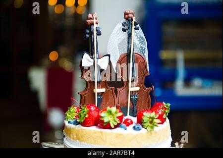 Essbare Figuren auf einem Kuchen in Form von zwei Violinen. Nahaufnahme - Stockfoto
