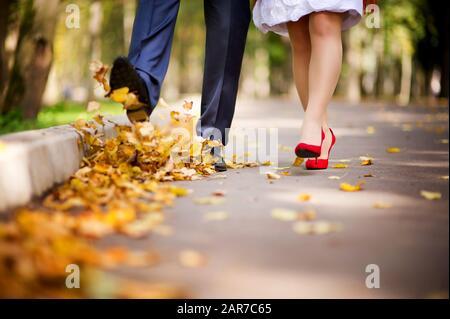 Das Paar geht im Herbst durch den Park und wirft mit den Füßen die gestürzten Blätter in die Luft. Tritt auf die Blätter. Nahaufnahme, keine Flächen - Stockfoto