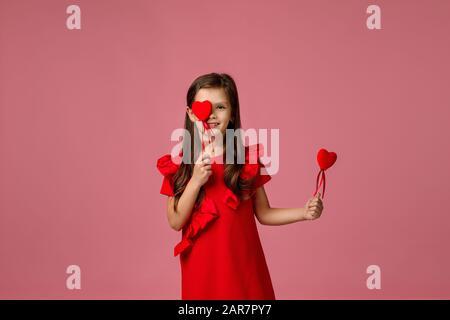 Valentinstag. Lächelndes Kindermädchen mit zwei roten Herzen isoliert auf pinkfarbenem Hintergrund. - Stockfoto
