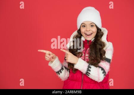 Wintermode. Kleines Mädchen lang lockiges Haar. Winterurlaub Ideen. Winteraktivität für Kinder. Glückliche Kindheit. Kaltes Wetter. Kind in Wollmützenmütze. Kinder fühlen sich eher kalt als Erwachsene. - Stockfoto