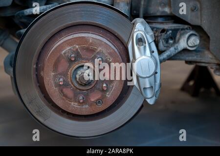 Das Bremssystem des Fahrzeugs, bei dem das Rad während der Wartung und beim Austausch in der Werkstatt am Fahrzeug mit Scheibe, Bremsbelägen, silberner Nabe ausgebaut wurde - Stockfoto