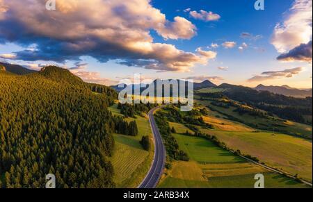 Straße, die bei Sonnenuntergang durch Wälder der Region Liptov in der Slowakei führt - Stockfoto