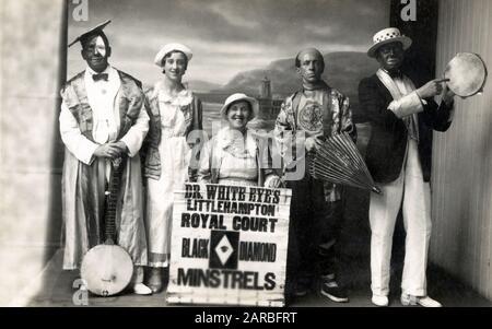 Dr. White Eye's Littlehampton Royal Court Black Diamond Minstrels - Minstrel Troupe, die Dr. White Eyes selbst in akademischen Gewändern umfasst und ein Banjo (ein Auge weiß, ein Schwarz), zwei joviale Damen, einen Chinaman und einen traditionelleren Minstrel mit Tamburin hält. Datum: 1937 - Stockfoto
