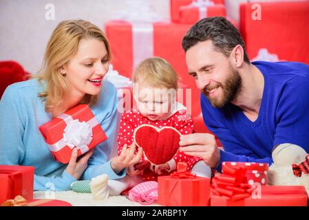 Online einkaufen. Dieses Herz ist für Sie. Liebe und Vertrauen in die Familie. Bärtiger Mann und Frau mit kleinem Mädchen. Glückliche Familie mit Geschenk, Vater, Mutter und Kind. Valentinstag. Rote Felder. - Stockfoto