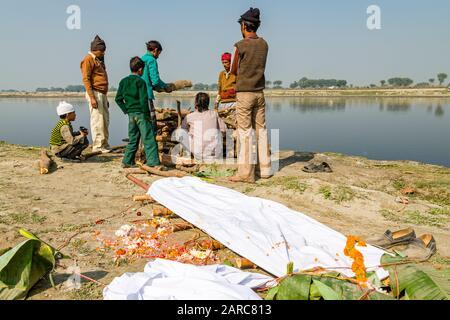 Eine Gruppe von Leuten, die die Zeremonie der Einäscherung eines Familienmitgliedes am Ufer des Flusses Yamuna beobachten - Stockfoto