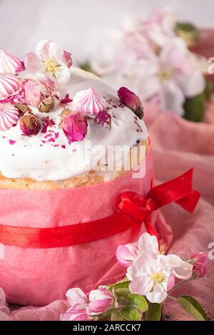 Fröhliche Osterdekoration für Grußkarte. Osterkuchen mit weißem Tüpfelchen, Marshmallows, trockenen Rosenblüten und rosenfarbenem Handwerkspapier. Vintage-Stil. - Stockfoto