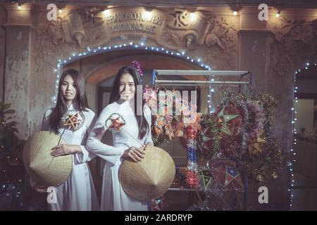 Zwei Schöne Frauen, die Ao Dai vietnamesisches traditionelles Kleid und den Tourismus zusammen im alten französischen Stil beim Weihnachtsfest von Sa tragen - Stockfoto