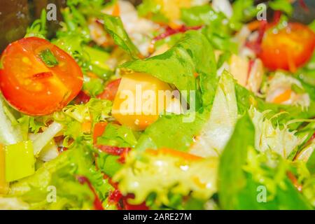 Gemüsesalat aus Tomaten, Gurken, Paprika, Zwiebeln, Arugula mit Käsewürfeln. Gesunde Ernährung, Fitnessdiät. Nahaufnahme - Stockfoto