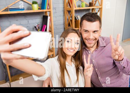 Junge Paare machen Fotos auf dem Smartphone und stachen mit zwei Fingern - Stockfoto