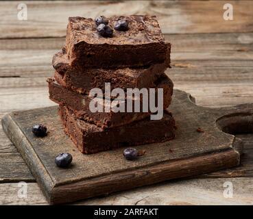 Stapel von Square gebackene Scheiben von Schokoladenkuchen Schokoladenkuchen mit Walnüssen auf einer hölzernen Oberfläche. Zubereitet hausgemachte Speisen. Gebäck Schokolade. Süße Speisen, Hausgemachte Stockfoto